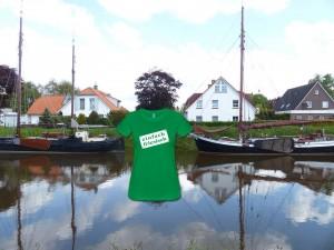 """Zwei Boote im Hafen von Carolinensiel, mit einem T-Shirt mit Motiv """"Einfach friesisch""""."""