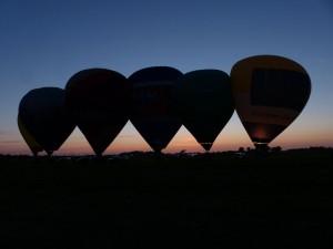Fünf Heißluftballons vor dem Sonnenuntergang auf einem Feld im Wangerland.
