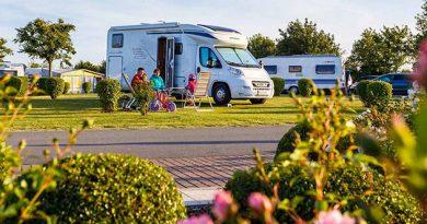 """ADAC Campingführer 2020: Insel-Camp Fehmarn (Meeschendorf, Deutschland)Auf dem Bild sitz eine Familie vor einem Wohnmobil. Quelle: """"obs/ADAC SE"""""""